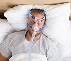 man using a CPAP or Bi-PAP machine in bed