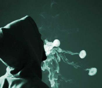 young male in green hoodie smoking